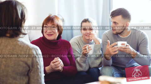 Купить «Portrait of happy family enjoying conversation over cup of coffee at home», видеоролик № 27385422, снято 20 декабря 2017 г. (c) Яков Филимонов / Фотобанк Лори