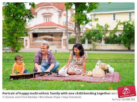 Portrait of happy multi-ethnic family with one child bonding together outdoors. Стоковое фото, фотограф Zoonar.com/Toni Rantala / easy Fotostock / Фотобанк Лори