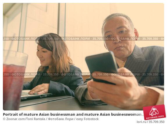 Portrait of mature Asian businessman and mature Asian businesswoman... Стоковое фото, фотограф Zoonar.com/Toni Rantala / easy Fotostock / Фотобанк Лори