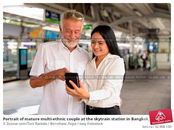 Portrait of mature multi-ethnic couple at the skytrain station in Bangkok, Thailand. Стоковое фото, фотограф Zoonar.com/Toni Rantala / easy Fotostock / Фотобанк Лори