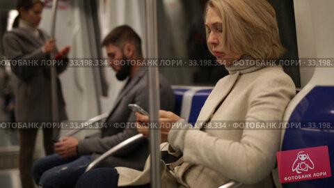 Купить «Portrait of mature woman absorbed in her smartphone while traveling in subway car», видеоролик № 33198334, снято 11 ноября 2019 г. (c) Яков Филимонов / Фотобанк Лори
