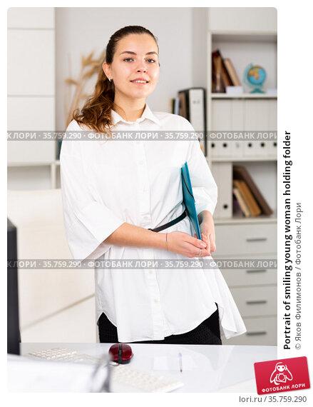 Portrait of smiling young woman holding folder. Стоковое фото, фотограф Яков Филимонов / Фотобанк Лори