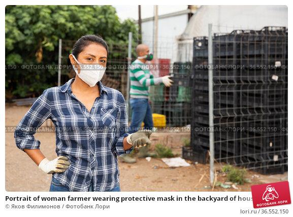 Portrait of woman farmer wearing protective mask in the backyard of house. Стоковое фото, фотограф Яков Филимонов / Фотобанк Лори