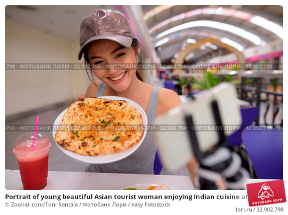Portrait of young beautiful Asian tourist woman enjoying Indian cuisine at the restaurant in Bangkok city. Стоковое фото, фотограф Zoonar.com/Toni Rantala / easy Fotostock / Фотобанк Лори