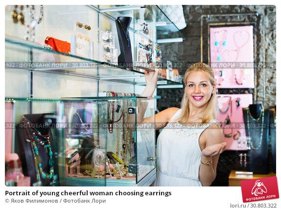 Купить «Portrait of young cheerful woman choosing earrings», фото № 30803322, снято 19 июня 2019 г. (c) Яков Филимонов / Фотобанк Лори