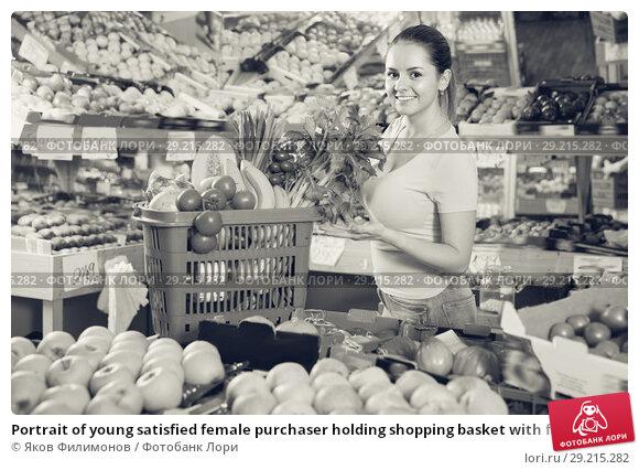Купить «Portrait of young satisfied female purchaser holding shopping basket with fruits and vegetables», фото № 29215282, снято 14 октября 2017 г. (c) Яков Филимонов / Фотобанк Лори