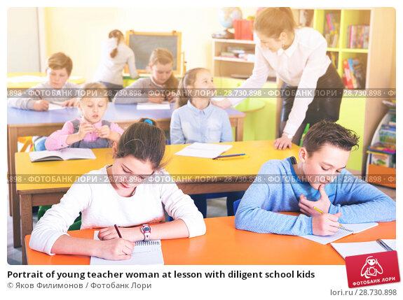 Купить «Portrait of young teacher woman at lesson with diligent school kids», фото № 28730898, снято 28 января 2018 г. (c) Яков Филимонов / Фотобанк Лори