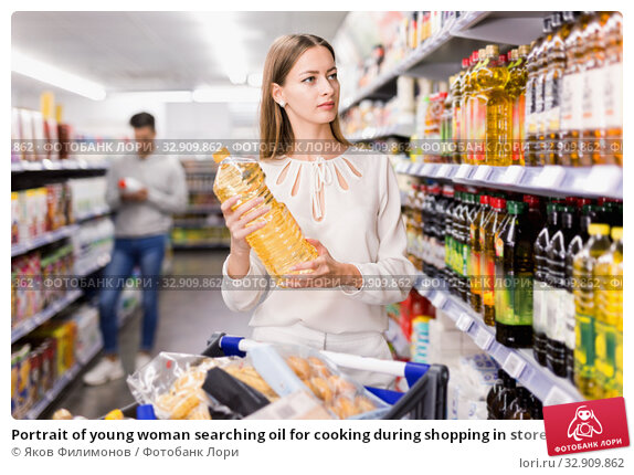 Купить «Portrait of young woman searching oil for cooking during shopping in store», фото № 32909862, снято 7 ноября 2019 г. (c) Яков Филимонов / Фотобанк Лори