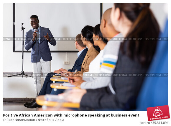 Positive African American with microphone speaking at business event. Стоковое фото, фотограф Яков Филимонов / Фотобанк Лори