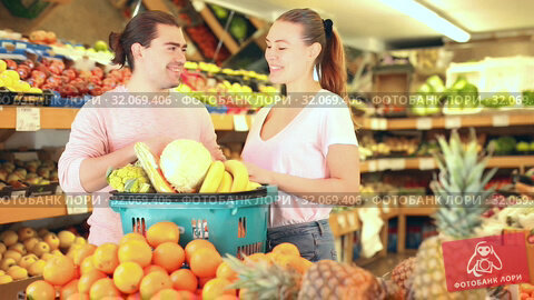 Купить «Positive family couple standing with full cart after shopping and pointing to shelves in fruit store», видеоролик № 32069406, снято 26 мая 2019 г. (c) Яков Филимонов / Фотобанк Лори