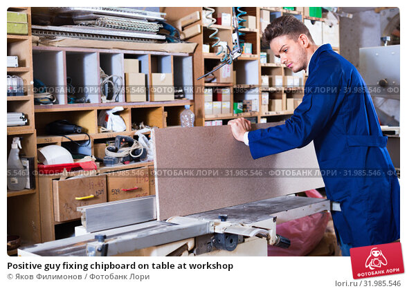 Купить «Positive guy fixing chipboard on table at workshop», фото № 31985546, снято 7 ноября 2016 г. (c) Яков Филимонов / Фотобанк Лори