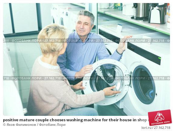Купить «positive mature couple chooses washing machine for their house in shop of household appliances», фото № 27162718, снято 26 апреля 2019 г. (c) Яков Филимонов / Фотобанк Лори