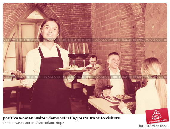 positive woman waiter demonstrating restaurant to visitors, фото № 25564530, снято 19 августа 2017 г. (c) Яков Филимонов / Фотобанк Лори