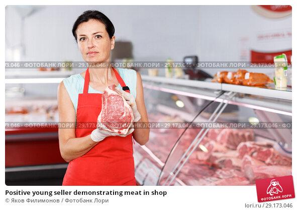 Купить «Positive young seller demonstrating meat in shop», фото № 29173046, снято 22 июня 2018 г. (c) Яков Филимонов / Фотобанк Лори