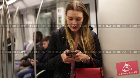 Купить «Positive young woman absorbed in her smartphone while traveling in subway car», видеоролик № 33403906, снято 17 января 2020 г. (c) Яков Филимонов / Фотобанк Лори