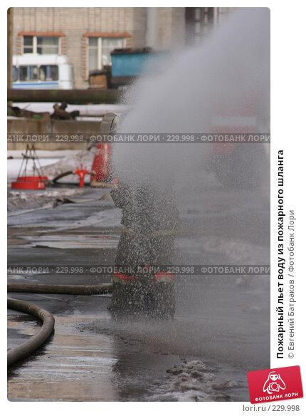 Пожарный льет воду из пожарного шланга, фото № 229998, снято 20 марта 2008 г. (c) Евгений Батраков / Фотобанк Лори