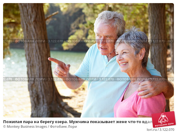 Купить «Пожилая пара на берегу озера. Мужчина показывает жене что-то вдалеке», фото № 3122070, снято 22 февраля 2011 г. (c) Monkey Business Images / Фотобанк Лори