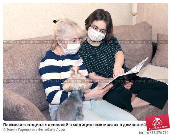 Пожилая женщина с девочкой в медицинских масках в домашней обстановке смотрят в книгу. Стоковое фото, фотограф Элина Гаревская / Фотобанк Лори