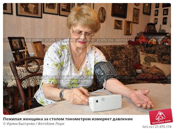 Купить «Пожилая женщина за столом тонометром измеряет давление», фото № 21975174, снято 19 января 2016 г. (c) Ирина Быстрова / Фотобанк Лори