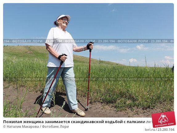 Пожилая женщина занимается скандинавской ходьбой с палками летом. Стоковое фото, фотограф Наталия Макарова / Фотобанк Лори