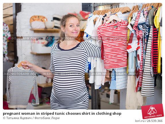 Купить «pregnant woman in striped tunic chooses shirt in clothing shop», фото № 28539366, снято 6 апреля 2017 г. (c) Татьяна Яцевич / Фотобанк Лори