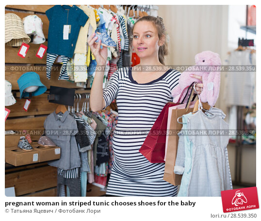 Купить «pregnant woman in striped tunic chooses shoes for the baby», фото № 28539350, снято 6 апреля 2017 г. (c) Татьяна Яцевич / Фотобанк Лори