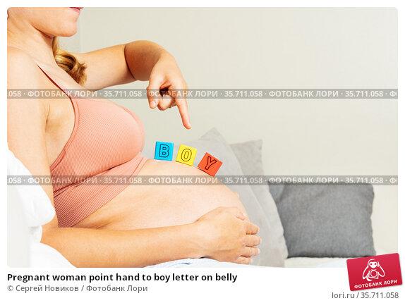Pregnant woman point hand to boy letter on belly. Стоковое фото, фотограф Сергей Новиков / Фотобанк Лори