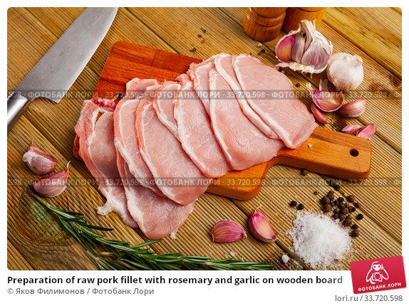 Купить «Preparation of raw pork fillet with rosemary and garlic on wooden board», фото № 33720598, снято 8 июля 2020 г. (c) Яков Филимонов / Фотобанк Лори