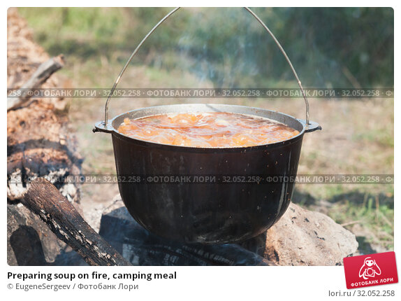 Preparing soup on fire, camping meal. Стоковое фото, фотограф EugeneSergeev / Фотобанк Лори