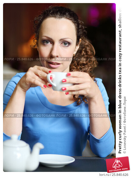 Купить «Pretty curly woman in blue dress drinks tea in cozy restaurant, shallow dof», фото № 25840626, снято 12 июля 2015 г. (c) Losevsky Pavel / Фотобанк Лори