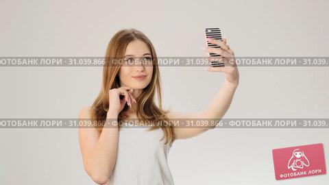 Pretty girl taking selfie with phone at studio slow motion. Стоковое видео, видеограф Denis Mishchenko / Фотобанк Лори
