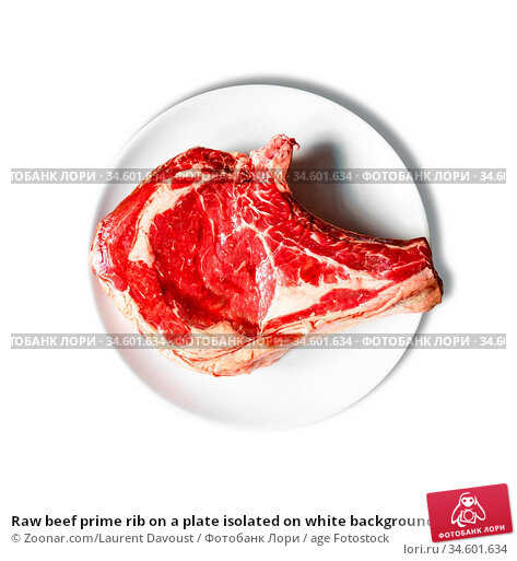 Raw beef prime rib on a plate isolated on white background. Top view. Стоковое фото, фотограф Zoonar.com/Laurent Davoust / age Fotostock / Фотобанк Лори