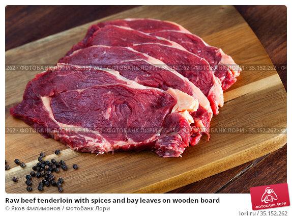 Raw beef tenderloin with spices and bay leaves on wooden board. Стоковое фото, фотограф Яков Филимонов / Фотобанк Лори