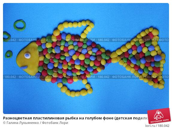 Разноцветная пластилиновая рыбка на голубом фоне (детская поделка), крупный план, иллюстрация № 180042 (c) Галина Лукьяненко / Фотобанк Лори