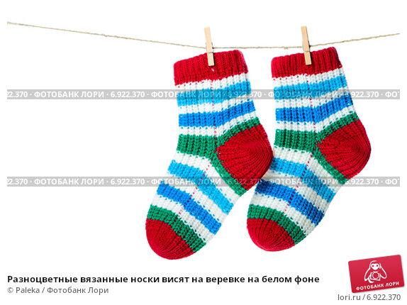 Купить «Разноцветные вязанные носки висят на веревке на белом фоне», фото № 6922370, снято 3 декабря 2014 г. (c) Paleka / Фотобанк Лори