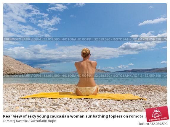 Rear view of sexy young caucasian woman sunbathing topless on romote pabble beach on Pag island, Croatia, Mediterranean. Стоковое фото, фотограф Matej Kastelic / Фотобанк Лори