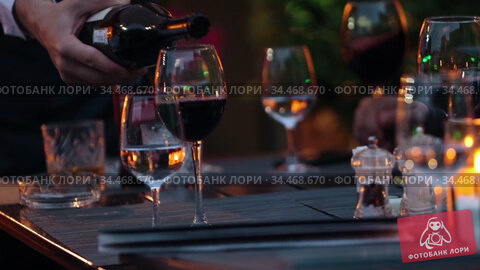 Restaurant's outdoor verandah - waiter pours wine into a glass while the corporate party. Стоковое видео, видеограф Константин Шишкин / Фотобанк Лори