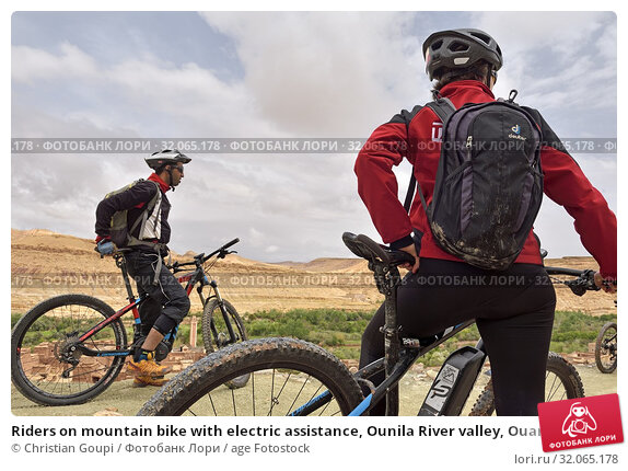 Riders on mountain bike with electric assistance, Ounila River valley, Ouarzazate Province, region of Draa-Tafilalet, Morocco, North West Africa. (2019 год). Редакционное фото, фотограф Christian Goupi / age Fotostock / Фотобанк Лори