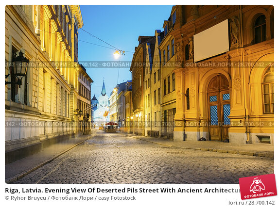Купить «Riga, Latvia. Evening View Of Deserted Pils Street With Ancient Architecture In Bright Warm Yellow Illumination Under Summer Blue Sky. Our Lady Of Sorrows Or Virgin Of Anguish Church In The Distance.», фото № 28700142, снято 1 июля 2016 г. (c) easy Fotostock / Фотобанк Лори