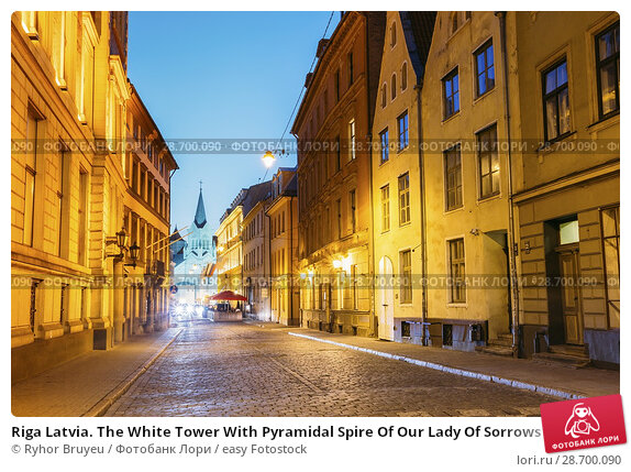 Купить «Riga Latvia. The White Tower With Pyramidal Spire Of Our Lady Of Sorrows Or Virgin Of Anguish Church, Ancient Catholic Church On Pils Street In Evening Illumination Under Summer Blue Sky.», фото № 28700090, снято 1 июля 2016 г. (c) easy Fotostock / Фотобанк Лори