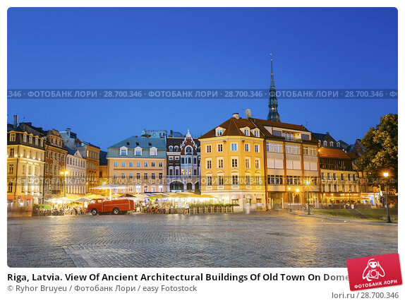 Купить «Riga, Latvia. View Of Ancient Architectural Buildings Of Old Town On Dome Square In Bright Evening Illumination, Popular Touristic Showplace With Outdoor Cafe In Summer Under Blue Sky.», фото № 28700346, снято 1 июля 2016 г. (c) easy Fotostock / Фотобанк Лори