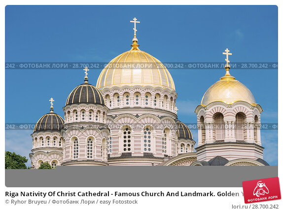 Купить «Riga Nativity Of Christ Cathedral - Famous Church And Landmark. Golden Yellow Domes On Blue Sunny Sky Background At Summer Season.», фото № 28700242, снято 1 июля 2016 г. (c) easy Fotostock / Фотобанк Лори