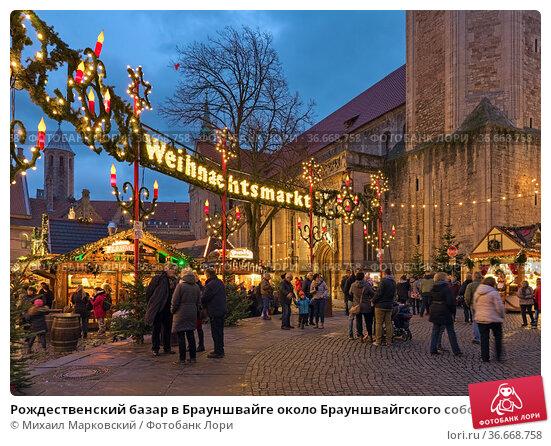 Рождественский базар в Брауншвайге около Брауншвайгского собора вечером, Германия (2018 год). Редакционное фото, фотограф Михаил Марковский / Фотобанк Лори