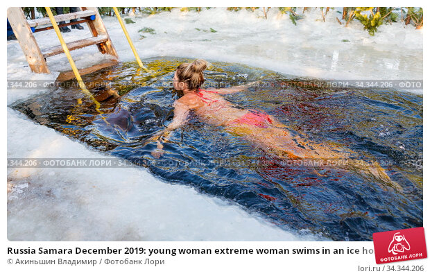 Russia Samara December 2019: young woman extreme woman swims in an ice hole in a winter day. Редакционное фото, фотограф Акиньшин Владимир / Фотобанк Лори