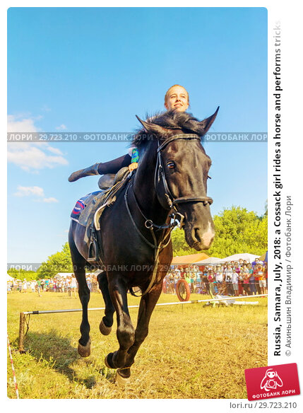 Купить «Russia, Samara, July, 2018: a Cossack girl rides a horse and performs tricks.», фото № 29723210, снято 29 июля 2018 г. (c) Акиньшин Владимир / Фотобанк Лори