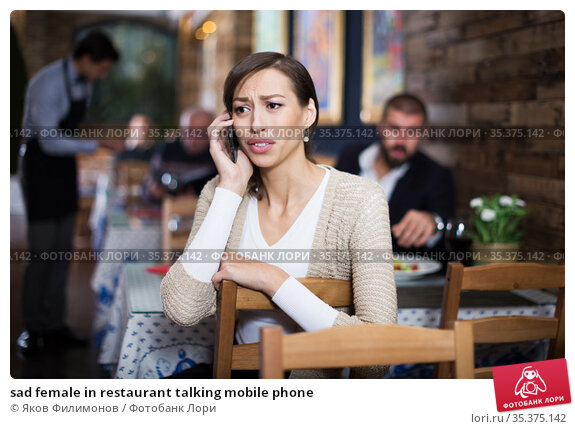sad female in restaurant talking mobile phone. Стоковое фото, фотограф Яков Филимонов / Фотобанк Лори