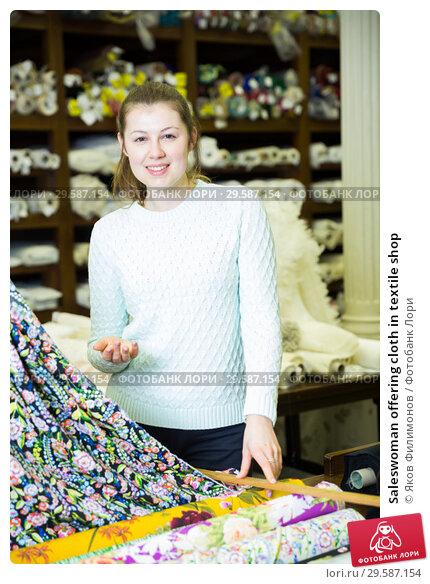 Купить «Saleswoman offering cloth in textile shop», фото № 29587154, снято 2 марта 2018 г. (c) Яков Филимонов / Фотобанк Лори