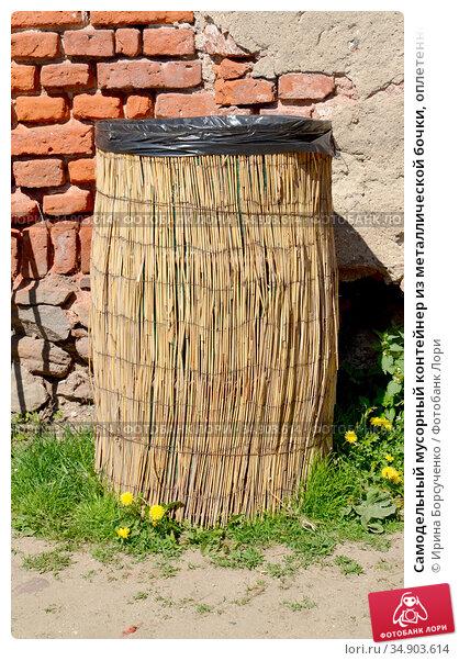 Самодельный мусорный контейнер из металлической бочки, оплетенной тростниковым матом. Стоковое фото, фотограф Ирина Борсученко / Фотобанк Лори