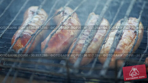 Купить «Sausages in the grill fry on coals. Flames make their way through the grille.», видеоролик № 30857286, снято 20 мая 2019 г. (c) Константин Мерцалов / Фотобанк Лори