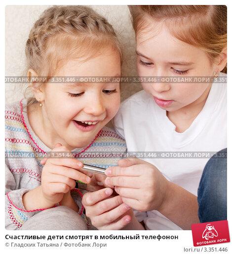 Счастливые дети смотрят в мобильный телефонон. Стоковое фото, фотограф Гладских Татьяна / Фотобанк Лори